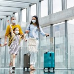 Family,With,Two,Children,Going,On,Holiday,,Wearing,Face,Masks